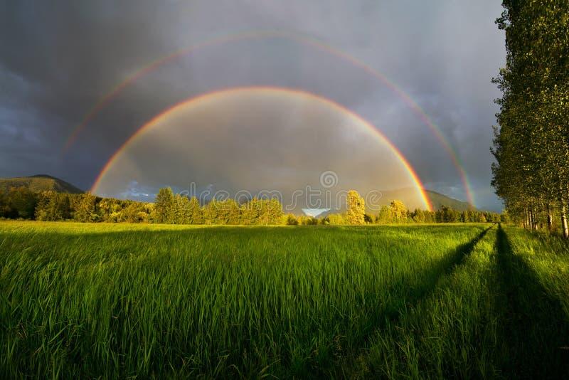 avsluta den dubbla regnbågen royaltyfri foto