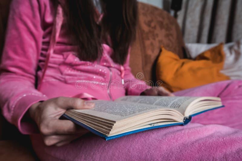 Avsluta sittande kvinnlig läsbok tjej som läser en bok på soffan Honhänder som håller i expanderad bok avslappnande hemma i royaltyfri fotografi