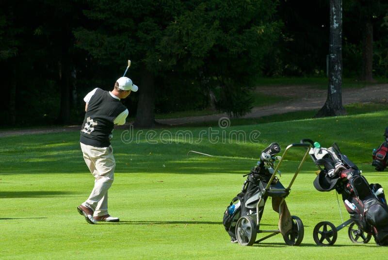 avslutar golfare hans swing royaltyfri bild