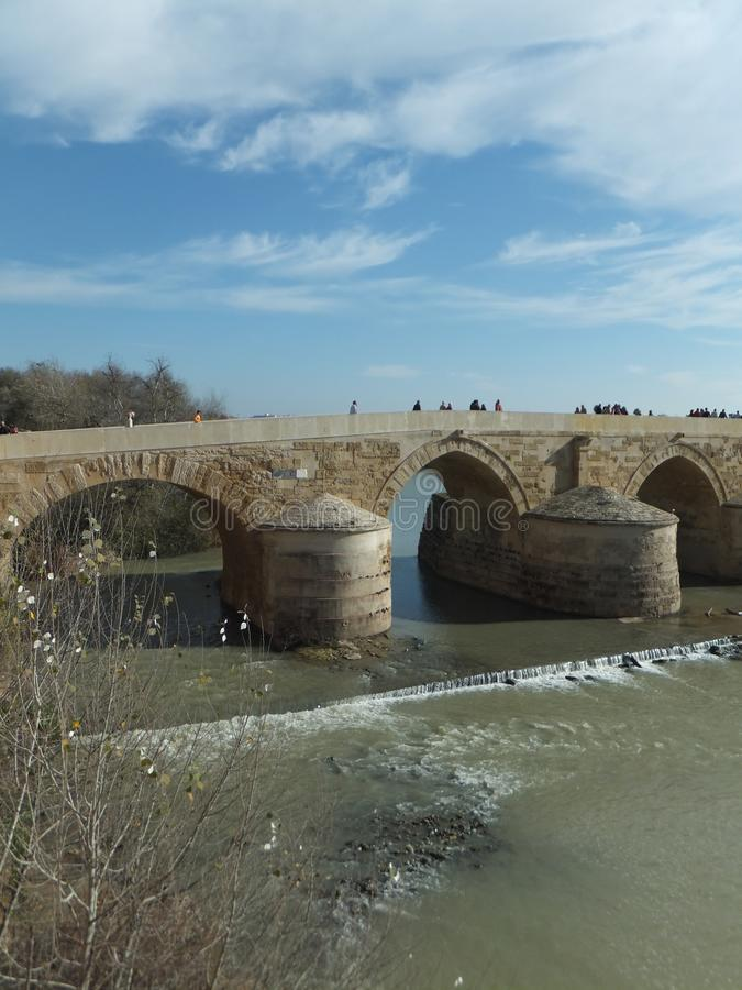 Avsnitt av Roman Bridge i Cordoba över den Guadalquivir floden på en ljus solig dag mot blå himmel med små diagram av folk arkivfoto