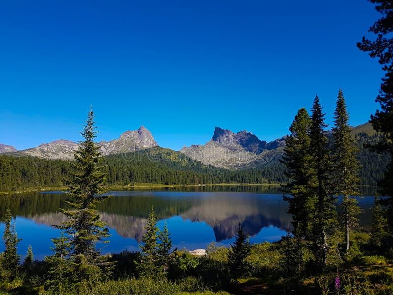 Avspegla yttersida av en sjö i bergen arkivbilder