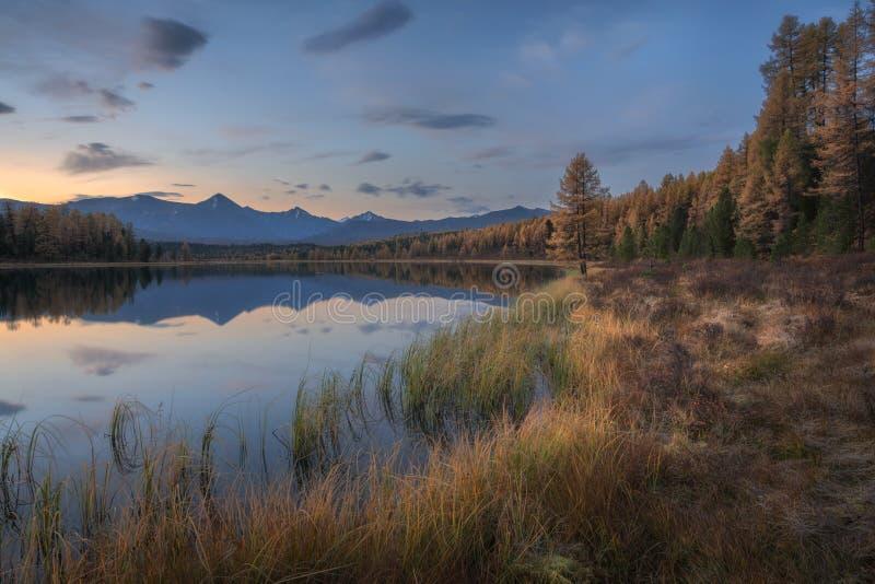 Avspegla yttersida sjön Autumn Landscape With Mountain Range på bakgrund med ljus - rosa himmel arkivbilder