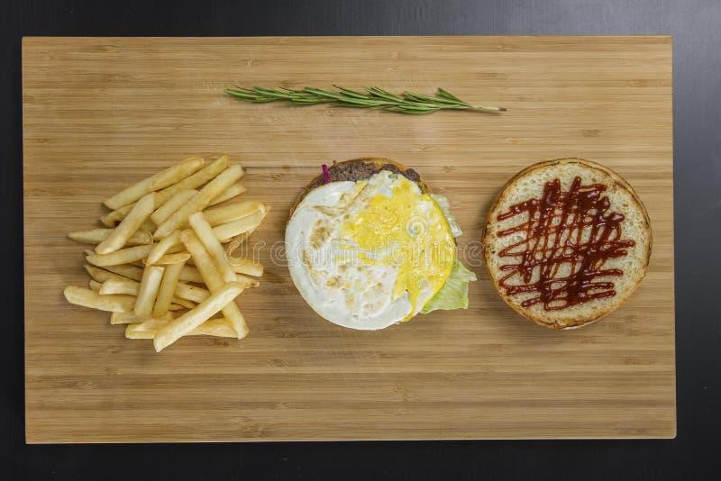 Avtäckt smaklig hamburgare med stekt ägg och potatis` s på tabellen royaltyfria bilder