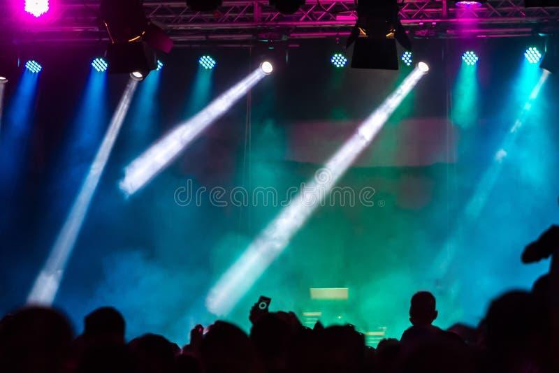 Avtala folkmassan som deltar i en konsert, folk som konturer är synliga, backlit av etappljus Lyftta händer och ilar telefoner är arkivbilder