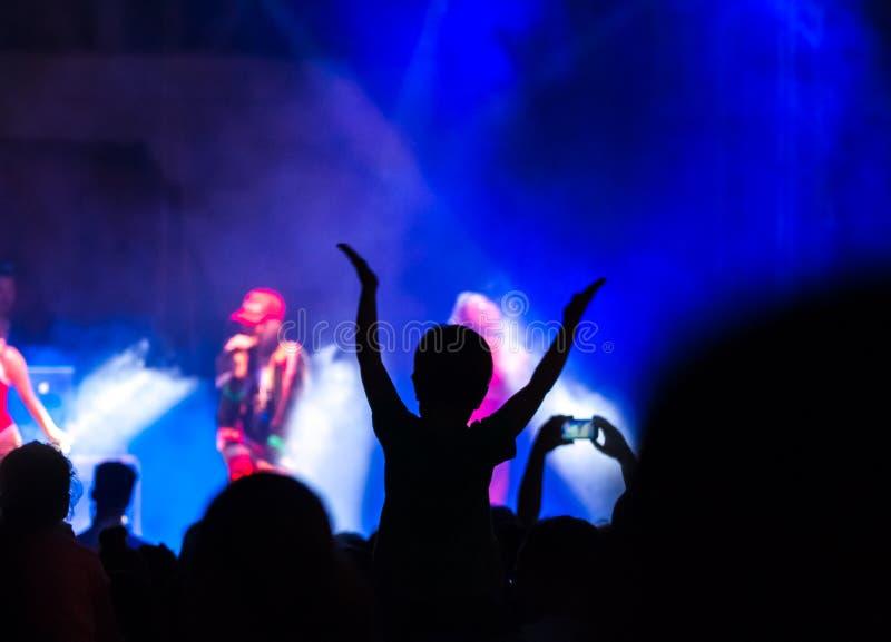 Avtala folkmassan som deltar i en konsert, folk som konturer är synliga, backlit av etappljus Lyftta händer och ilar telefoner är royaltyfri foto