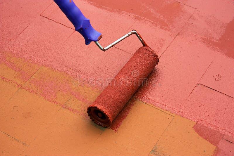 Avtala målaren som målar ett golv med en målarfärgrulle royaltyfri fotografi