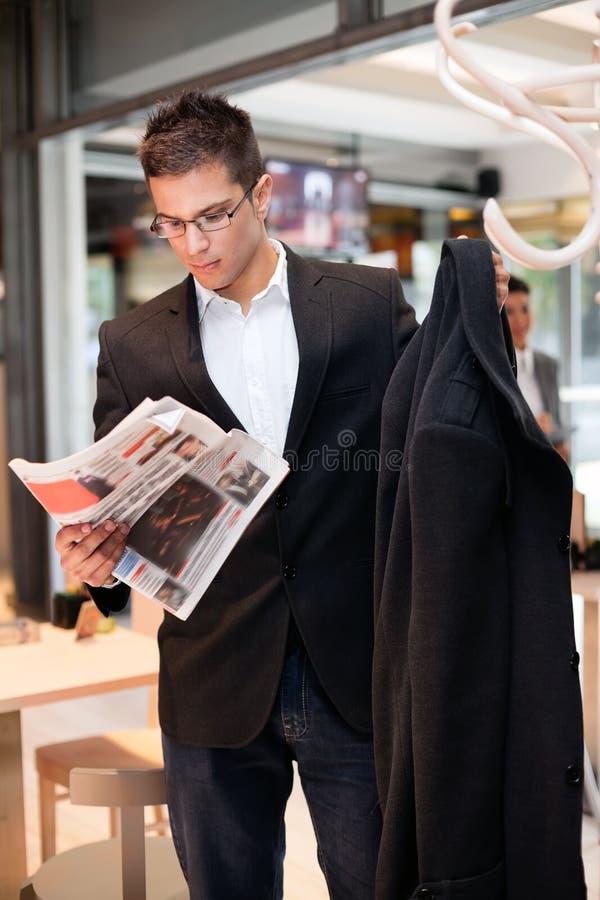 Avtalad ung man för affär läsa tidningen royaltyfri bild