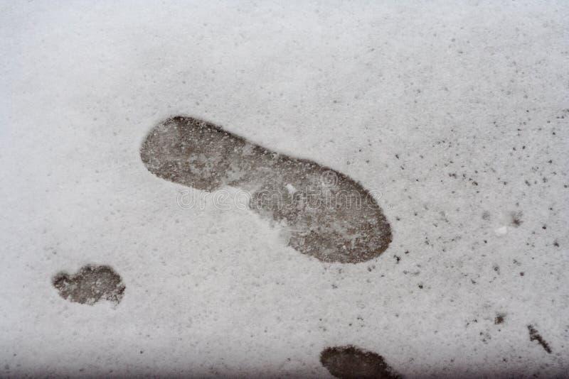 Avtryck av en sko på vit snö arkivfoto