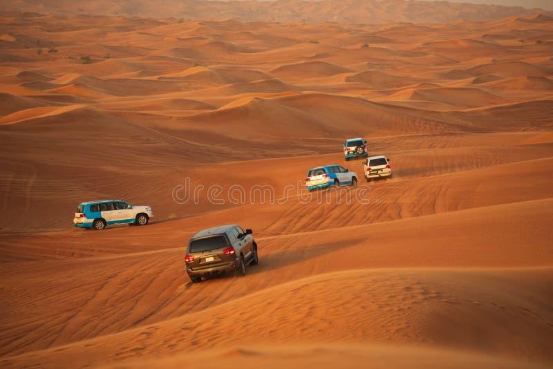 Avventura fuori strada con SUVs che guida nel deserto arabo al tramonto Spettacolo tradizionale per i turisti con colpire del vei fotografia stock