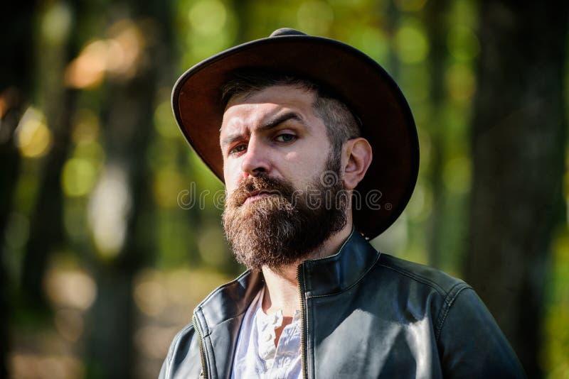 Avventure del cowboy Fondo barbuto della natura del cowboy dell'uomo defocused Cowboy brutale con la barba lunga Turista dei pant immagine stock libera da diritti