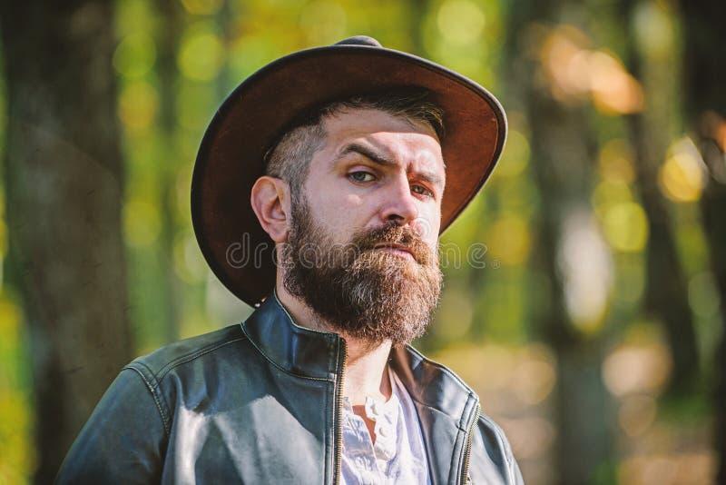 Avventure del cowboy Fondo barbuto della natura del cowboy dell'uomo defocused Cowboy brutale con la barba lunga Turista dei pant fotografia stock