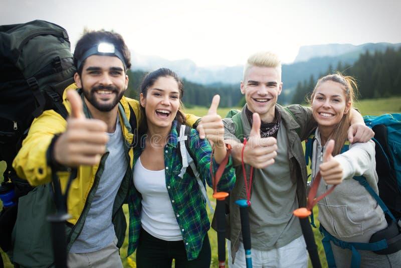 Avventuri, viaggi, turismo, aumento e concetto della gente - gruppo di amici sorridenti con gli zainhi e la mappa all'aperto fotografia stock libera da diritti