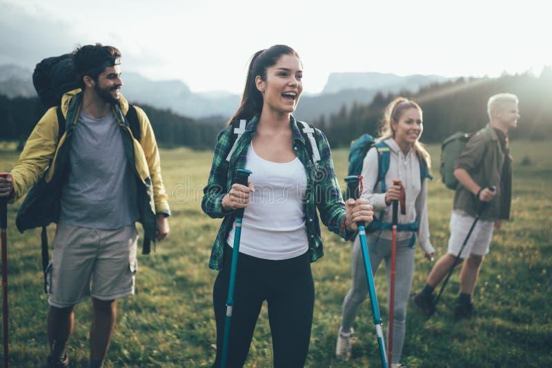 Avventuri, viaggi, turismo, aumento e concetto della gente - gruppo di amici sorridenti con gli zainhi e la mappa all'aperto immagine stock