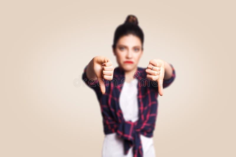avversione La giovane ragazza infelice di ribaltamento con i capelli del panino e di stile casuale sfoglia giù il suo dito, sulla immagine stock