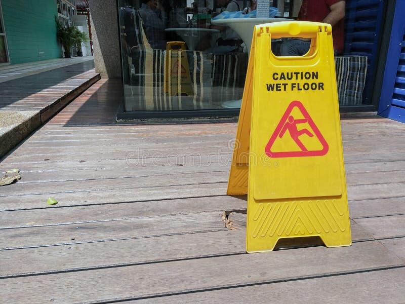 Avverta il segnale di pericolo del pavimento bagnato con vago sul pavimento di legno fotografia stock libera da diritti