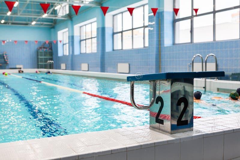 Avviare la piattaforma con il numero due è in una piscina per i gruppi dei bambini Pratica dei bambini con l'istruttore fotografia stock