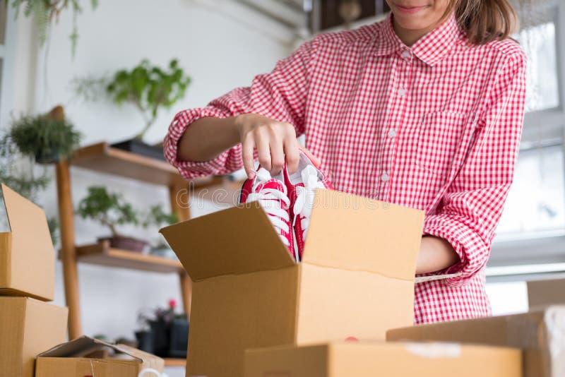 Avvii sulle scarpe dell'imballaggio del piccolo imprenditore nella scatola a workpl fotografie stock libere da diritti