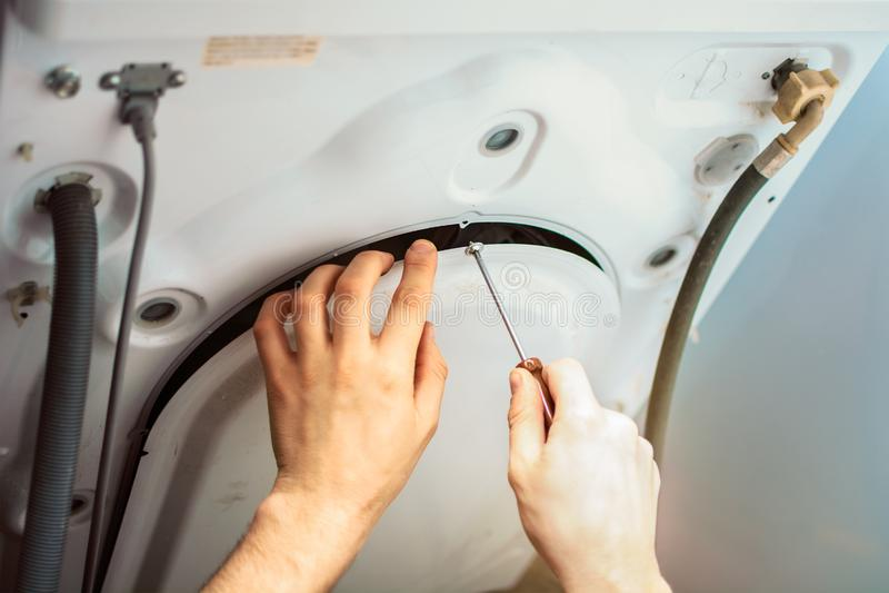 Avvitando la copertura della lavatrice con un cacciavite a poppa immagini stock libere da diritti