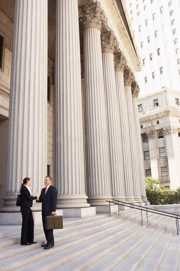Avvocati che stringono le mani sui punti del tribunale immagine stock libera da diritti