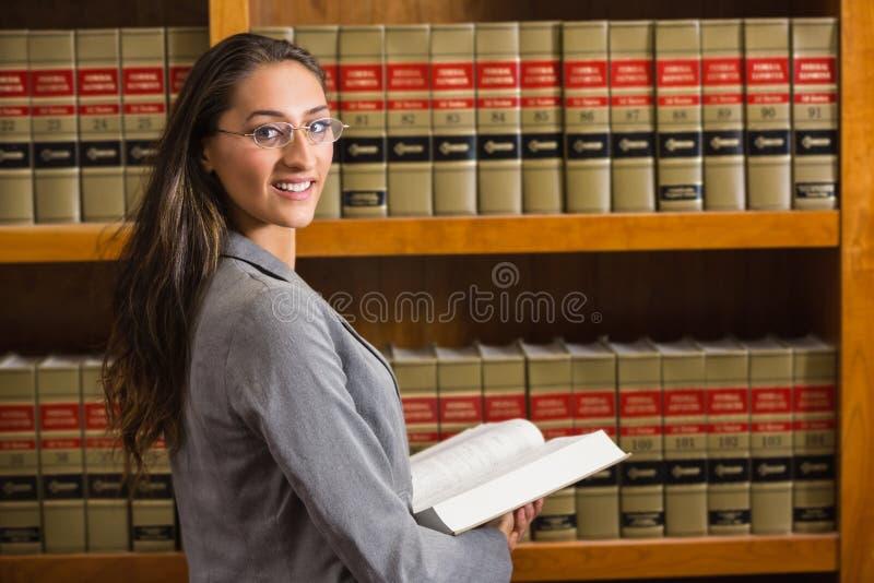 Avvocato che esamina macchina fotografica nella biblioteca di legge fotografia stock
