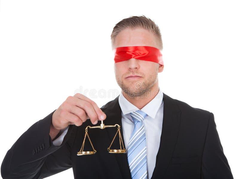 Avvocato con la bilancia della giustizia che indossa una benda immagine stock