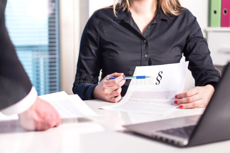Avvocato femminile ed avvocato che indicano un documento giuridico nella riunione fotografie stock