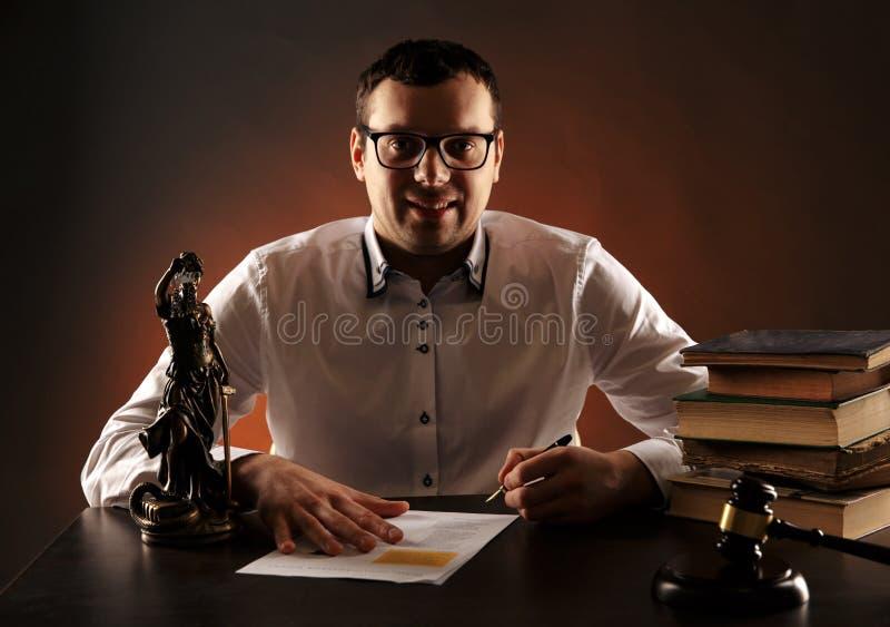 Avvocato maschio sorridente sul suo scrittorio con lavoro di ufficio Bilancia e martelletto e libri di legno fotografia stock