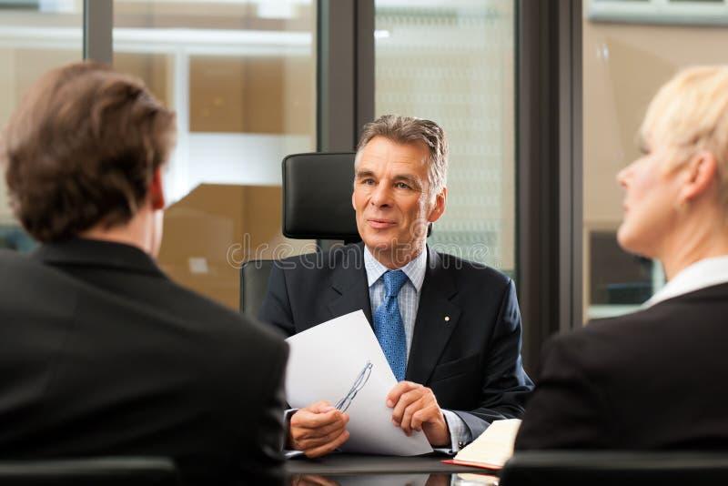 Avvocato o notaio con i clienti nel suo ufficio fotografia stock