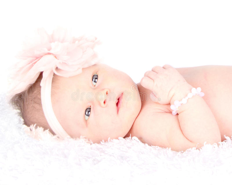 An awake newborn laying on a blanket. An awake newborn girl with blue eyes laying on a blanket stock photography