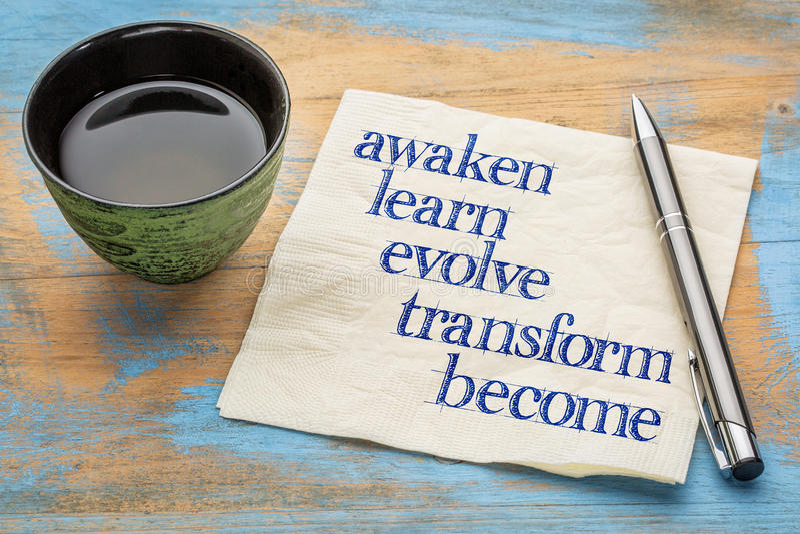 Awaken, learn, evolve, transform, become. Awaken, learn, evolve, transform and become - inspirational words - handwriting on a napkin with a cup of tea stock photos