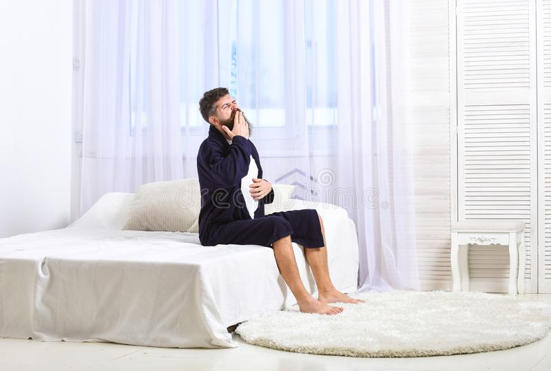 Awakening concept. Man in robe sits on bed, white curtains on background. Macho with beard and mustache sluggish getting. Up and yawning in morning. Guy on royalty free stock image