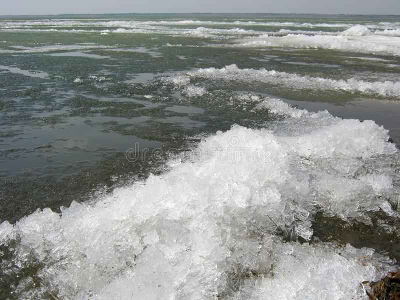 Early spring The lake is free of ice. In the foreground, beautiful ice-frozen waves. royalty free stock photos