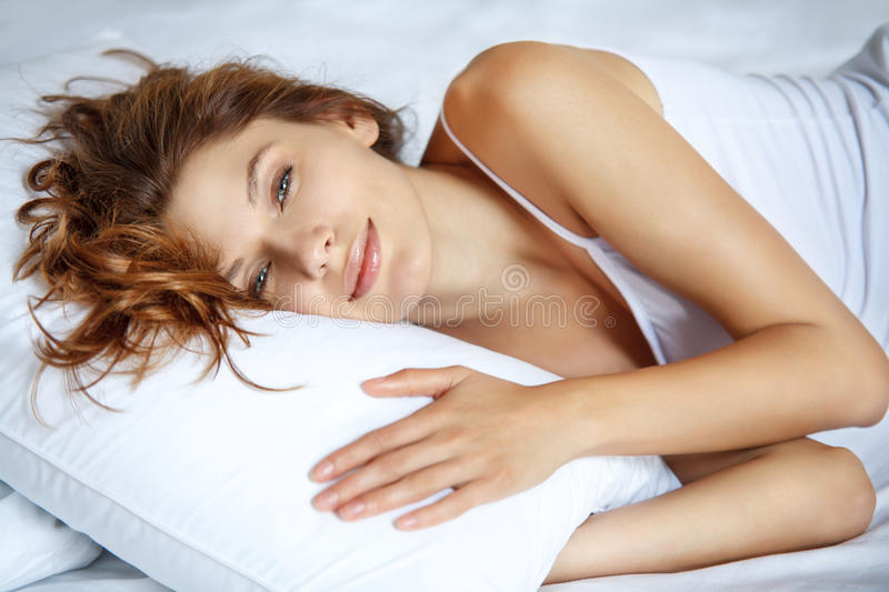 Awakening women in bed. Beautiful brunette woman lying on a pillow royalty free stock images