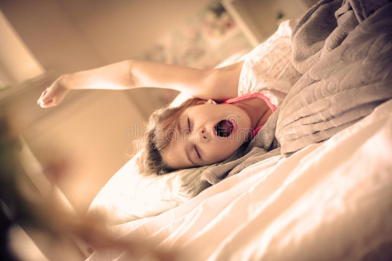 Awaking. Child in bed. Little girl wake up in bed. Space for copy royalty free stock photo