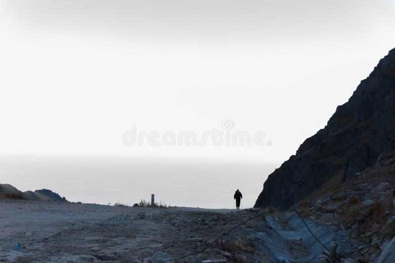 Awanturniczy mężczyzna stoi na górze góry i cieszy się pięknego widok podczas wibrującego zmierzchu obraz stock