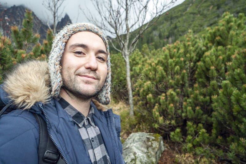 Awanturniczy młody człowiek w górach podczas zimnej pogody fotografia stock