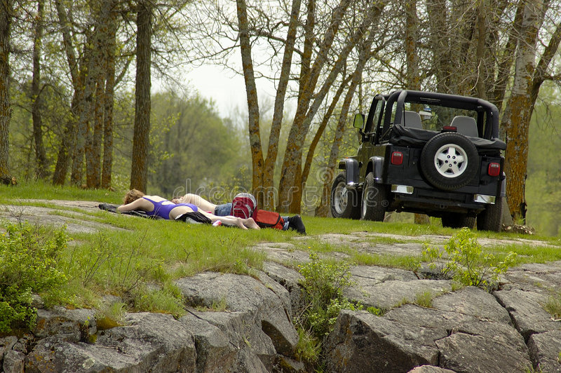 Away From it All. A couple relaxing on a sunny bank beside their jeep royalty free stock image