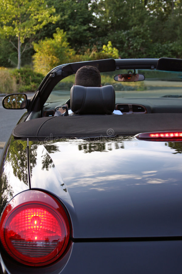 Away We Go. Brake lights of an expensive convertible with a man getting ready to drive away stock photo