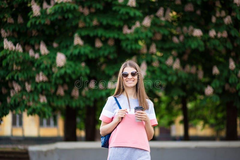 away kaffetake Den härliga flickan i solglasögon med ryggsäcken går vid sommargatan med kaffe royaltyfri fotografi
