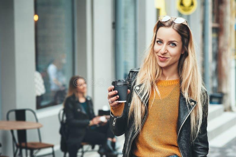 away kaffetake Härlig ung stads- kvinna som bär i stilfull kläder som rymmer kaffekoppen och ler, medan gå royaltyfria foton