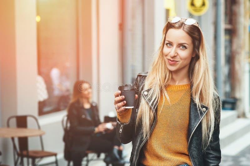 away kaffetake Härlig ung stads- kvinna som bär i stilfull kläder som rymmer kaffekoppen och ler, medan gå arkivbild