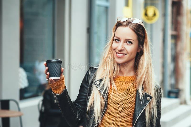 away kaffetake Härlig ung stads- kvinna som bär i stilfull kläder som rymmer kaffekoppen och ler, medan promenera sten arkivbild
