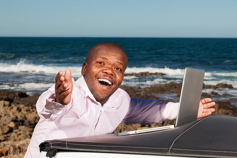 Awe in technology. African dwarfman standing at the back of a pickup truck with his arms flung open in awe while working the computer royalty free stock photos