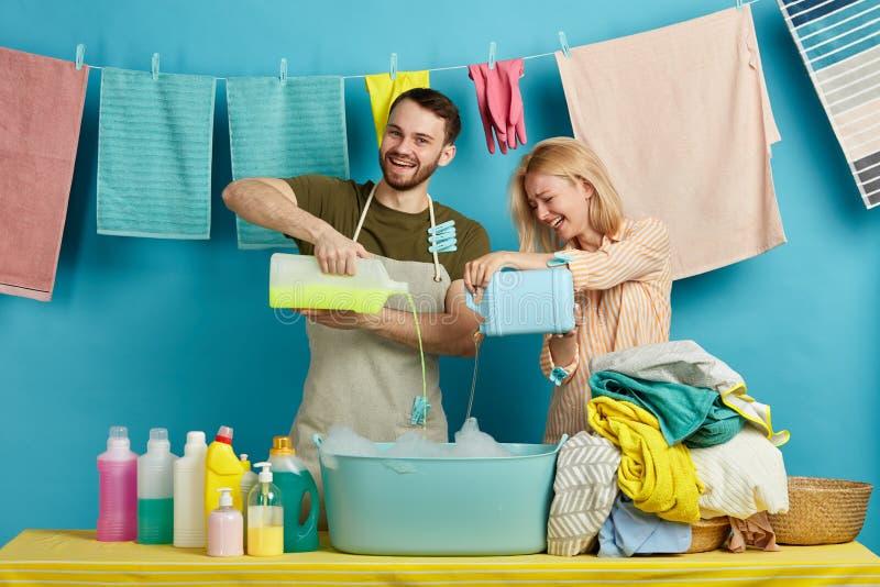 Awesoem kobieta w fartuchach ma zabawę i młody człowiek podczas gdy robić pianie dla myć obrazy stock
