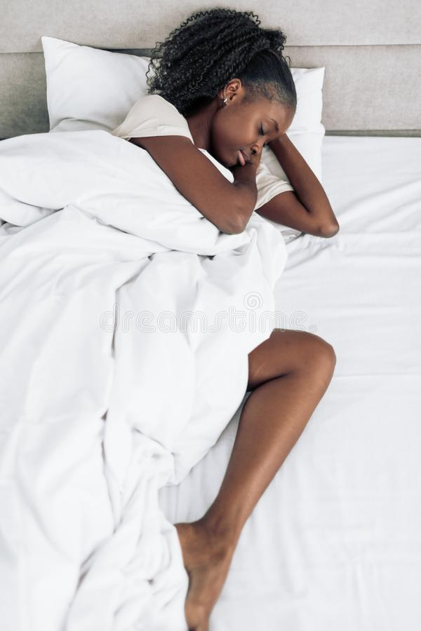 Awesome african girl sleeping in her bed at night stock photos