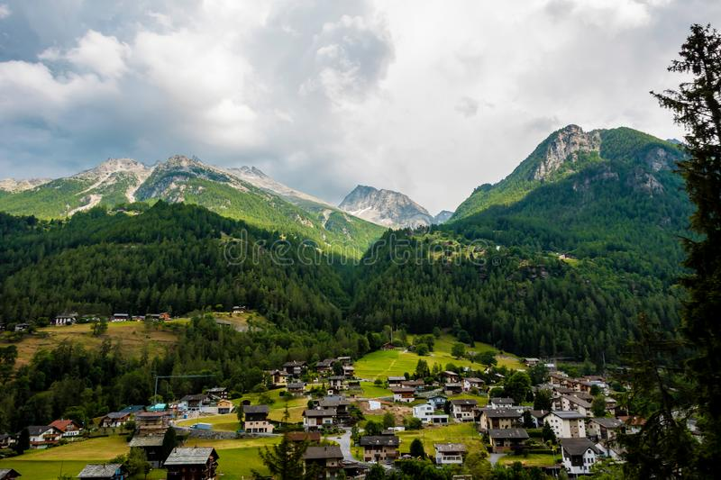 Awesome alpine highlands. Breathtaking view of swiss village and mountains in the background. View from panoramic train stock photos