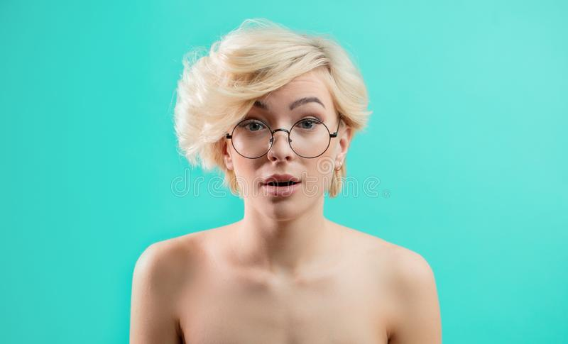 Awesome blond girl in glasses looks surprised. As she has forgotton something important. shock, disbelief, misunderstanding concept stock image