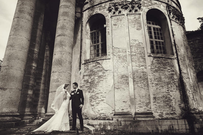 Awesome couple stands behind a ruined wall of an old cathedral stock photos