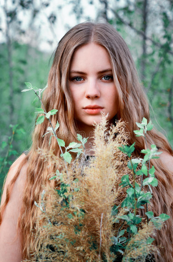 Awesome,excellent,beautiful,nice girl with long,straight,light hair. The portrait of spring girl in green trees,flowers,garden,park.Long-haired light-haired royalty free stock images