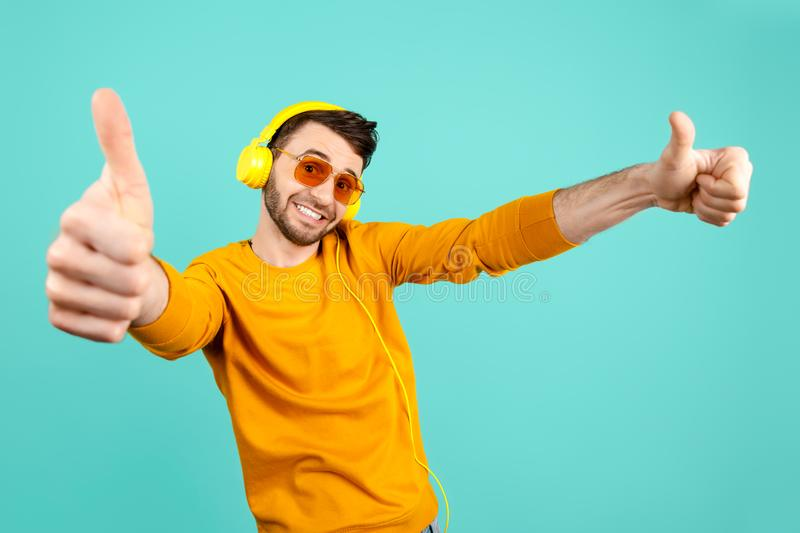 Awesome funny bearded young man wearing yellow sunglasses listening to music with yellow headphones showing ok gesture stock photography